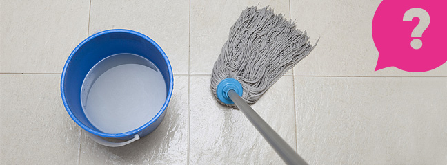 A mop and bucket on a slippery tiled floor
