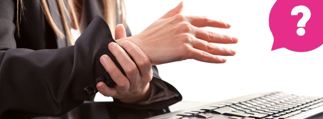 woman holding her wrist in pain at her desk