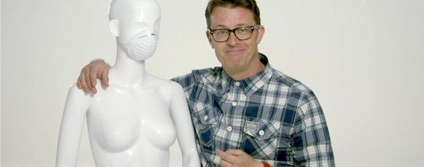 A man with his hand on the shoulder of a mannequin