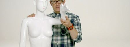 A man holding up the arm of a mannequin showing its wrist